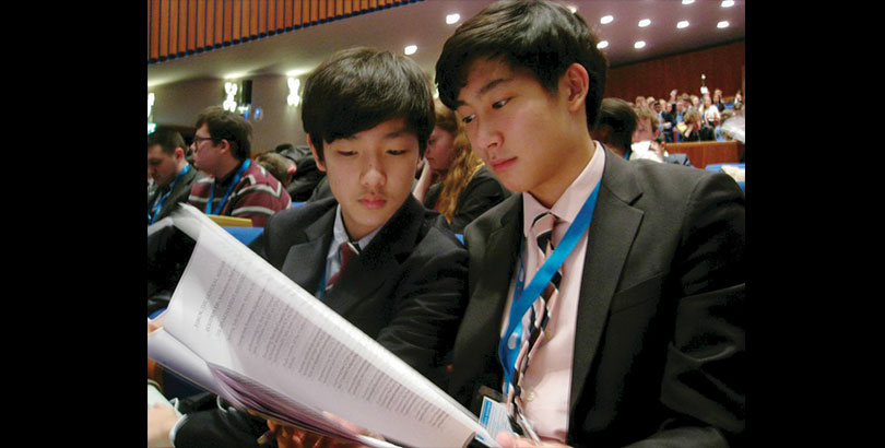 Photo by Jasmine Oh (10)  Glancing over the given resolution packet, Jeffrey Heo (9) and Ryan Jang (9)  prepare themselves for the General Assembly plenary session.