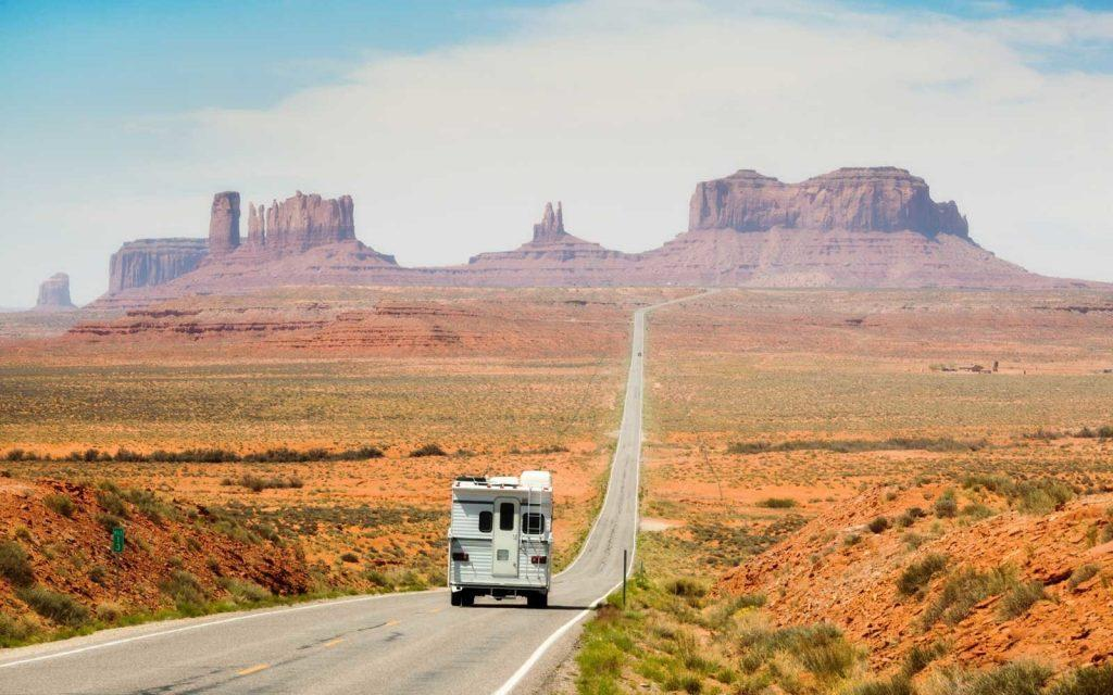 Pickup camper recreational vehicle touring the American Southwest on a highway road trip near Monument Valley Tribal Park. Along the Utah and Arizona border, USA. The sandstone plateaus and rock formations are a campus place and travel destination for family vacations.