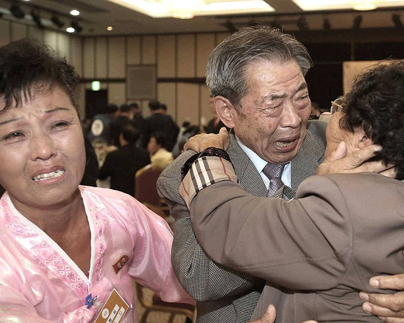 South Korean Min Ho-shik, 84, center, hugs his North Korean family member Min Un Sik, right, during the Separated Family Reunion Meeting at Diamond Mountain resort in North Korea, Tuesday, Oct. 20, 2015. Hundreds of elderly Koreans from divided North and South began three days of reunions Tuesday with loved ones many have had no contact with since the war between the countries more than 60 years ago. At left is an unidentified family member of North Korean Min.(Kim Do-hoon/Yonhap via AP) KOREA OUT